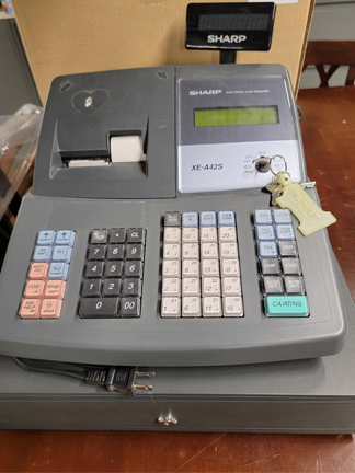Photo of a dark gray cash register with multi-colored buttons.